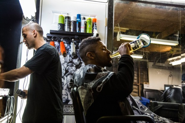 Jason replacing one of his clipper attachments while his client enjoys a refreshment. Photo by Randy Vazquez
