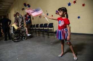 Alexia Martinez waves her American flag as she waits for her uncle Marco Martinez's arrival. Photo by Randy Vazquez.