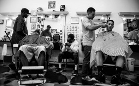 """Derrick Dyer, 25, looks up at his fellow barber at """"Pro Style's"""" barbershop in San Jose, Calif. (Randy Vazquez)"""