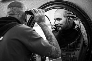 "A barber at ""Kingsley's"" barbershop in San Jose, Calif. cuts his hair in the early morning prior to the arrival of his clients. (Randy Vazquez)"