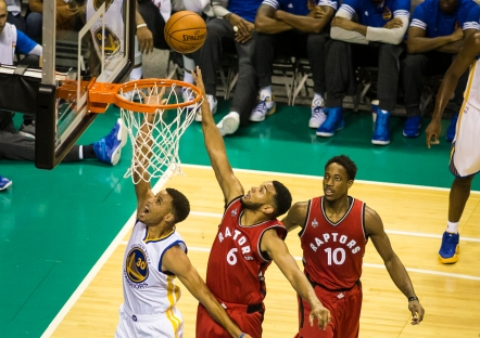 Reigning NBA most valuable player Golden State Warriors point guard Stephen Curry drives past a pair of Toronto Raptors defenders for a layup during his teams 95-87 preseason opening victory on Oct. 5, 2015 at SAP Center in San Jose, Calif. (Randy Vazquez)