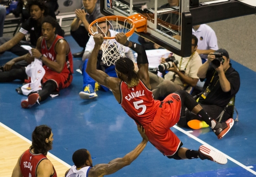 Toronto Raptors small forward DeMarre Carroll soars over Golden State Warriors small forward Andre Iguodala for an alley-oop dunk on Oct. 5, 2015 at SAP Center in San Jose, Calif. The Warriors would go on to win the preseason exhibition 95-87. (Randy Vazquez)