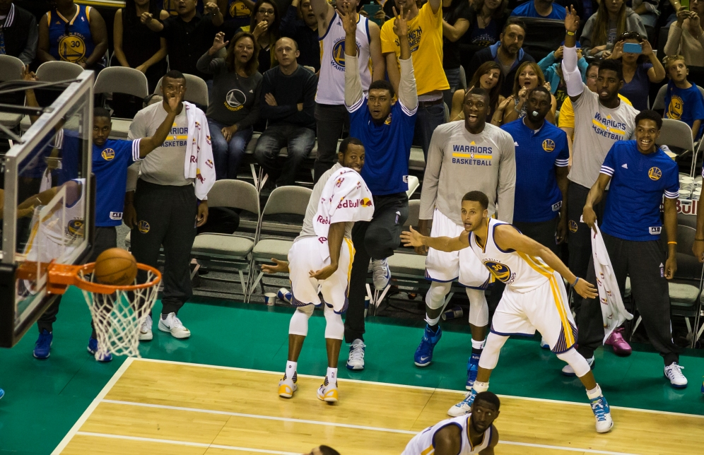 Golden State Warriors point guard Stephen Curry is coated in cheers as the reigning NBA most valuable player scores a three-point shot and slaps teammate Andre Iguodala's hand prior to the ball entering the basket. The Warriors would go on to win the preseason opening match 95-87 on Oct. 5, 2015 at SAP Center in San Jose, Calif. Randy Vazquez, Spartan Daily