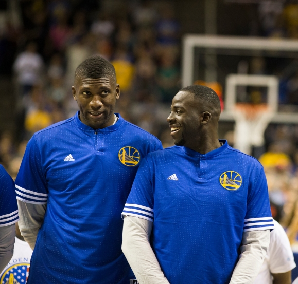 Golden State Warriors back up center Festus Ezeli, left, and forward Draymond Green, right, converse prior to the start of their team's preseason opening match versus the Toronto Raptors on Oct. 5, 2015 at SAP Center in San Jose, Calif. (Randy Vazquez)