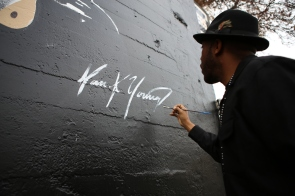 """Muralist Ian Young signs his work during the unveiling of the """"Interview with an Icon"""" mural in Downtown San Jose, Calif. on Dec. 2, 2015. Young worked day and night for five weeks to complete the project. (Randy Vazquez)"""