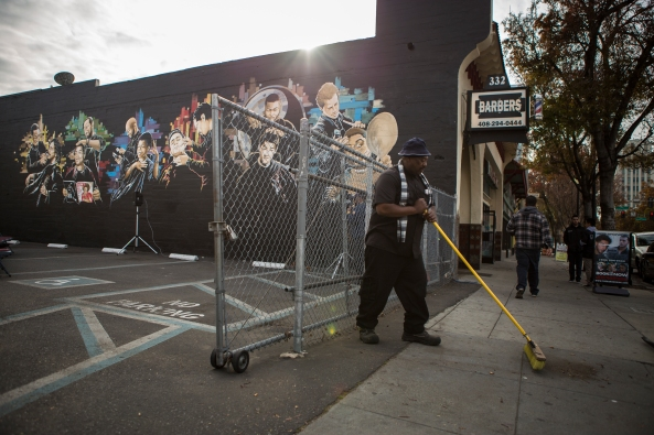 """William Whitt sweeps in front of the """"Interview with an Icon"""" mural in Downtown San Jose, Calif. on Dec. 2, 2015. The mural features barbers from Barbers Inc. barbershop providing barber services to cultural icons. (Randy Vazquez)"""
