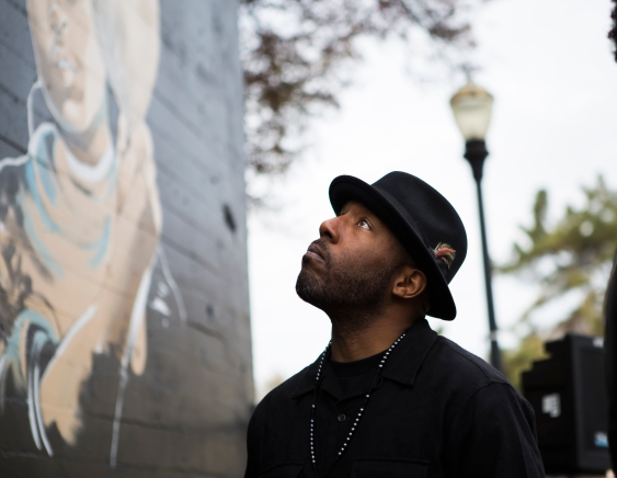 """Ian Young looks at the """"Interview with an Icon"""" mural that took him five weeks to complete. The piece features six barbers from the Barbers Inc. barbershop providing barbering services to six cultural icons on Dec. 2, 2015 in San Jose, Calif. (Randy Vazquez)"""