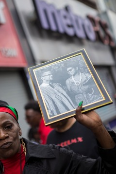 "A woman holds up a black and white photograph of Malcolm X during the ""Shut'em Down"" Black Power March in Harlem, N.Y. on May 19, 2016. Many cities around the county observe this date as Malcolm X Day. (Randy Vazquez)"