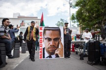 """Led by a portrait of human rights activist Malcolm X supporters walked up and down 125th Street in Harlem, N.Y. during the """"Shut'em Down"""" Black Power March on May 19, 2016. (Randy Vazquez)"""