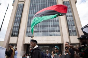 """Participants of the """"Shut'em Down"""" Black Power March walk past the Adam Clayton Powell Jr. State Office Building in Harlem, N.Y. on May 19, 2016. (Randy Vazquez)"""