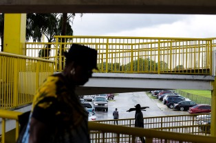 Marie Bierre walks down to the parking area on a rainy day at Fort Lauderdale Swamp Shop on July 2, 2016. Randy Vazquez, Sun Sentinel