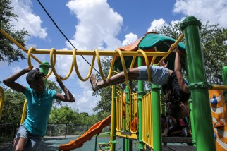 Pascale Prosper, left, and Addy Williamson, right, hangout at the jungle gym during the Coral Springs Police Department summer feeding program and camp at Hunt Elementary on Tuesday, July 19, 2016. The police department coordinates the staffing, education enrichment components, sports activities and food distribution. Randy Vazquez, Sun Sentinel