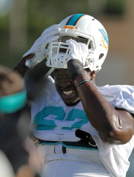 Rookie first round draft pick Laremy Tunsil (67) puts on his helmet during Miami Dolphins training camp in Davie on Aug. 5, 2016. Randy Vazquez, Sun Sentinel