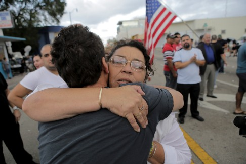 Maria Garrido, hugs one of members the crowd of people that gathered on Eight Street in Little Havana on Nov. 26, 2016. Garrido joined the crowd of people celebrating the death of Fidel Castro. Randy Vazquez, Sun-Sentinel