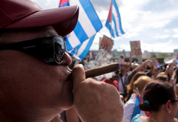 Roberto Giraldo smokes a cigar during the celebration of the death of Fidel Castro in the streets of Little Havana on Nov. 26, 2016. Randy Vazquez, Sun-Sentinel