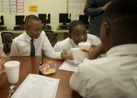 Some students at Forest Park Elementary in Boynton Beach are learning to be gracious young men during the Gentleman's Club, which meets after school every other Tuesday. Jevenson Antoine, left, tries to make a toast with his club mates. Randy Vazquez, Sun-Sentinel