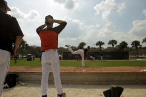 Miami Marlins pitchers and catchers began spring training Tuesday at Roger Dean Stadium in Jupiter. Manager Don Mattingly, left, watches Justin Nicolino (20), right, throw a pitch during training. Other positions groups also showed up to workout. Randy Vazquez, South Florida Sun-Sentinel