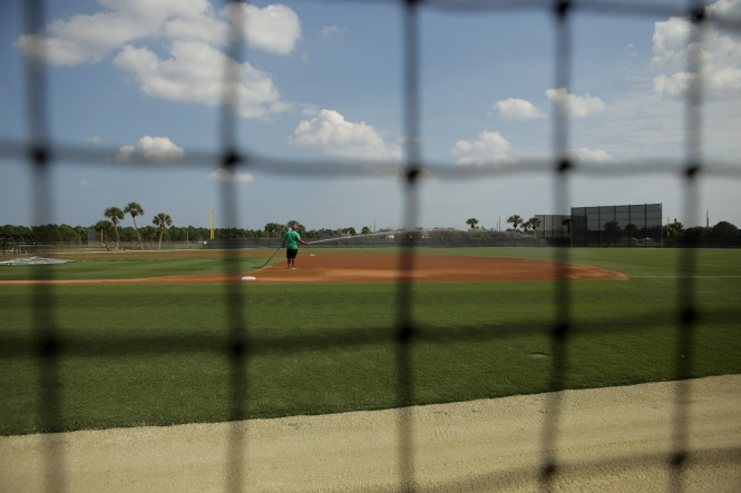 Mitchell Moenster waters one of the fields behind Roger Dean Stadium in Jupiter. The Miami Marlins pitchers and catchers began spring training Tuesday at Roger Dean Stadium. Other positions groups also showed up to workout. Randy Vazquez, South Florida Sun-Sentinel