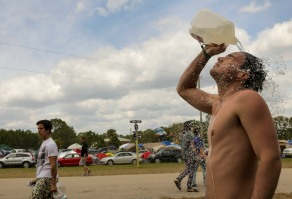 Kendall Dickson, right, takes a quick shower at Okeechobee Music and Arts Festival on Sunday afternoon. Randy Vazquez, SouthFlorida.Com