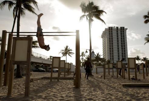 Ryan Anderson, left, hangs upside down during a workout at Fort Lauderdale Beach on April 18, 2017. Randy Vazquez, South Florida Sun-Sentinel