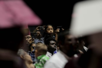 A child is seen in the crowd between two caps during the Lake Worth Community High School graduation at the Expo Center in the South Florida Fairgrounds in West Palm Beach on Friday, May 19, 2017. Randy Vazquez South Florida Sun-Sentinel