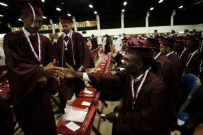 Correntheus Hicks, right, shakes hands with fellow classmates as they begin to line up for the Lake Worth Community High School graduation at the Expo Center in the South Florida Fairgrounds in West Palm Beach on Friday, May 19, 2017. Randy Vazquez South Florida Sun-Sentinel