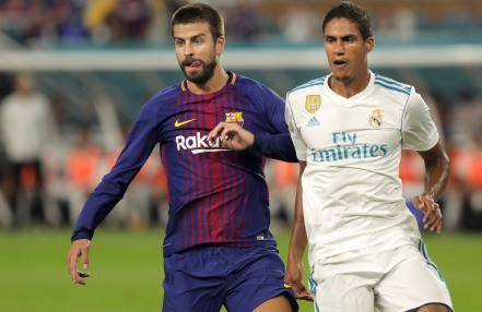 Barcelona defender Gerard Pique, left, and Real Madrid defender Raphael Varane, right, jockey for position during Saturday nights game at Hard Rock Stadium. Randy Vazquez, South Florida Sun-Sentinel