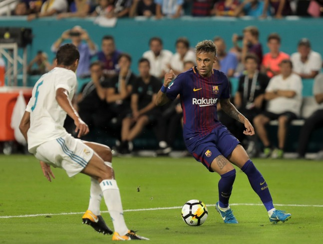 Barcelona forward Neymar, right, dribbles passed Real Madrid defender Raphael Varane, left, Saturday night at Hard Rock Stadium. Randy Vazquez, South Florida Sun-Sentinel