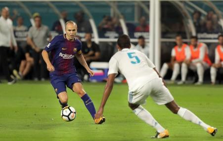 Barcelona midfielder Andres Iniesta, left, dribbles passed Real Madrid defender Raphael Varane, right, Saturday night at Hard Rock Stadium. Randy Vazquez, South Florida Sun-Sentinel