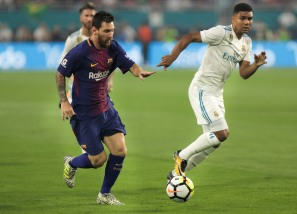 Barcelona's Lionel Messi, left, runs passed Real Madrid midfielder Casemiro, right, Saturday nights game at Hard Rock Stadium. Randy Vazquez, South Florida Sun-Sentinel