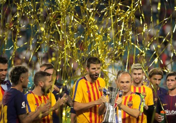 Barcelona midfielder Andres Iniesta holds a trophy presented to his team after defeating rival Real Madrid on Saturday night at Hard Rock Stadium.