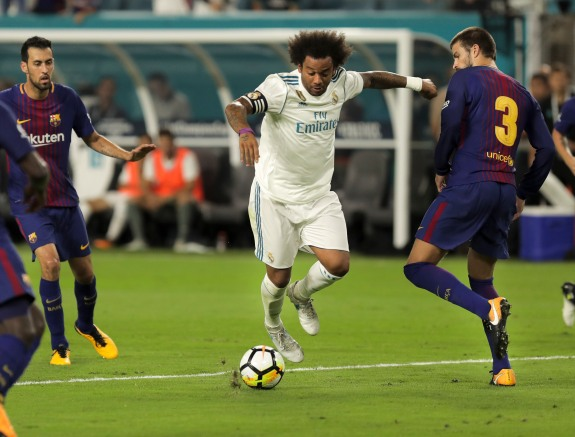 Real Madrid defender Marcelo, center, dribbles passed defenders during Saturday night's game versus rival Barcelona at Hard Rock Stadium. Randy Vazquez, South Florida Sun-Sentinel