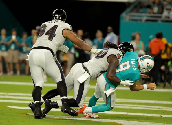 Miami Dolphins quarterback David Fales (9), right, gets tackled in the end zone after making a pass by Baltimore Ravens outside linebacker Za'Darius Smith (90), left, during Thursday night's game at Hard Rock Stadium. Randy Vazquez, South Florida Sun-Sentinel