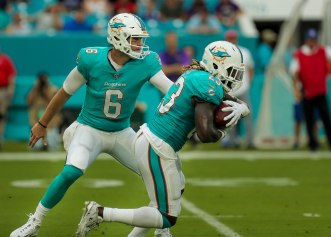 Miami Dolphins quarterback Jay Cutler (6), left, hands the ball off to running back Jay Ajayi (23), right, during Thursday night's game versus the Baltimore Ravens at Hard Rock Stadium. Randy Vazquez, South Florida Sun-Sentinel