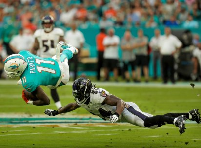 Miami Dolphins wide receiver DeVante Parker (11), left, flies through the air after being tackled by Baltimore Ravens cornerback Brandon Carr (24), right, during Thursday night's game versus the Baltimore Ravens at Hard Rock Stadium. Randy Vazquez, South Florida Sun-Sentinel