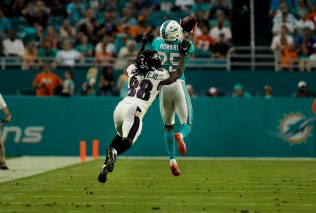 Miami Dolphins cornerback Xavien Howard(25) makes an interception over Baltimore Ravens wide receiver Quincy Adeboyejo (88) during Thursday night's game at Hard Rock Stadium. Randy Vazquez, South Florida Sun-Sentinel