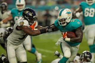 Miami Dolphins running back Senorise Perry (34), right, tries to avoid a tackle from Baltimore Ravens safety Chuck Clark (36), left, during Thursday night's game at Hard Rock Stadium. Randy Vazquez, South Florida Sun-Sentinel