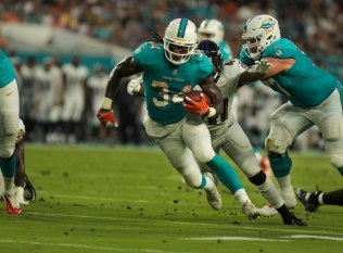 Miami Dolphins running back Senorise Perry (34) runs through a gap during Thursday night's game at Hard Rock Stadium. Randy Vazquez, South Florida Sun-Sentinel