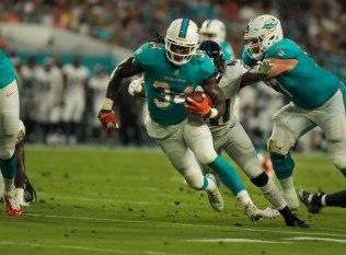 Miami Dolphins running back Senorise Perry (34) runs through a gap during Thursday night's game at Hard Rock Stadium. Randy Vazquez, South Florida Sun-Sentinel