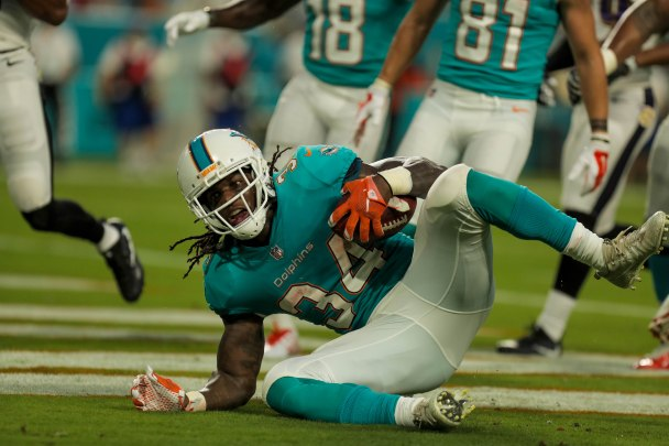Miami Dolphins running back Senorise Perry (34) scores the opening touchdown during Thursday night's game at Hard Rock Stadium. Randy Vazquez, South Florida Sun-Sentinel