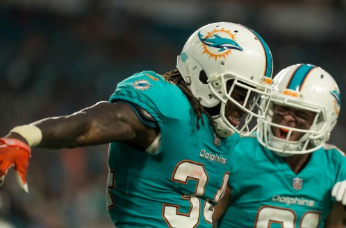 Miami Dolphins running back Senorise Perry (34) celebrates after scoring the opening touchdown during Thursday night's game at Hard Rock Stadium. Randy Vazquez, South Florida Sun-Sentinel
