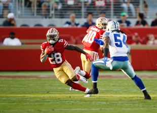 San Francisco 49ers' Jerick McKinnon (28), left, runs away from Dallas Cowboys' Jaylon Smith (54), right, in the first quarter of their preseason NFL game at Levi's Stadium in Santa Clara, Calif., on Thursday, Aug. 9, 2018. (Randy Vazquez/ Bay Area News Group)