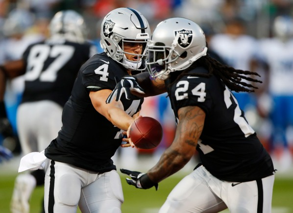 Oakland Raiders quarterback Derek Carr (4), left, hands the ball off to Marshawn Lynch (24), right, in the first quarter of their preseason NFL game at the Coliseum in Oakland, Calif., on Friday, Aug. 10, 2018. (Randy Vazquez/ Bay Area News Group)