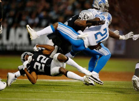 Oakland Raiders' Rashaan Melvin (22), left, and Derrick Johnson (56), center, tackle Detroit Lions' Ameer Abdullah (21), right, in the first quarter of their preseason NFL game at the Coliseum in Oakland, Calif., on Friday, Aug. 10, 2018. (Randy Vazquez/ Bay Area News Group)
