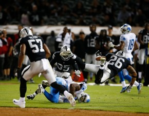 Oakland Raiders' Shalom Luani (26), right, flies over Detroit Lions' Marcus Lucas (86), center, after he makes a catch in the fourth quarter of their preseason NFL game at the Coliseum in Oakland, Calif., on Friday, Aug. 10, 2018. The Raiders would win the game 16-10 over the Lions. (Randy Vazquez/ Bay Area News Group)