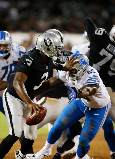 Oakland Raiders quarterback EJ Manuel (3), left, stiff arms Detroit Lions' Freddie Bishop (49), right, in the fourth quarter of their preseason NFL game at the Coliseum in Oakland, Calif., on Friday, Aug. 10, 2018. The Raiders would win the game 16-10 over the Lions. (Randy Vazquez/ Bay Area News Group)