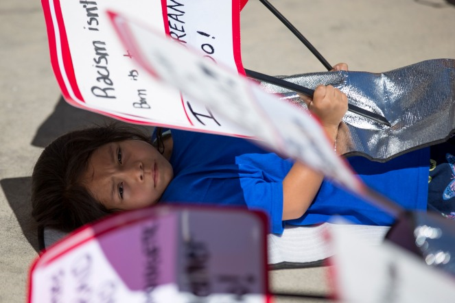 "Estef Fuentes, 5, lays on the ground covered in a shinny blanket during a demonstration at a ""Families Belong Together"" rally in San Jose, Calif., on Saturday, June 30, 2018. Several rallies were held across the country to protest family separation at the U.S.-Mexico border under President Trump's ""zero tolerance"" policy. Fuentes along with three other members of Grupo la Solidaridad placed shiny blankets over themselves as they lay on the ground to show how many children at detention centers sleep. (Randy Vazquez/ Bay Area News Group)"