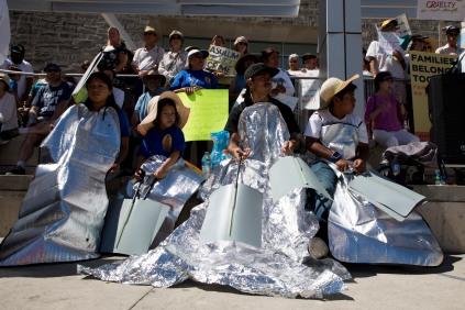 """Members of Grupo la Solidaridad cover themselves with blankets to represent the many children at U.S. Customs and Border Protection detention centers who sleep under mylar blankets during a """"Families Belong Together"""" rally in San Jose, Calif., on Saturday, June 30, 2018. Several rallies were held across the country to protest family separation at the U.S.-Mexico border under President Trump's """"zero tolerance"""" policy. (Randy Vazquez/ Bay Area News Group)"""