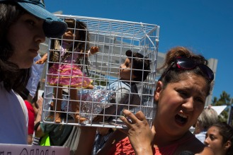 "Christina Rodriguez, right, carries a cage with two dolls in it to represent the children who are currently in detention centers during a ""Families Belong Together"" rally in San Jose, Calif., on Saturday, June 30, 2018. Several rallies were held across the country to protest family separation at the U.S.-Mexico border under President Trump's ""zero tolerance"" policy. (Randy Vazquez/ Bay Area News Group)"