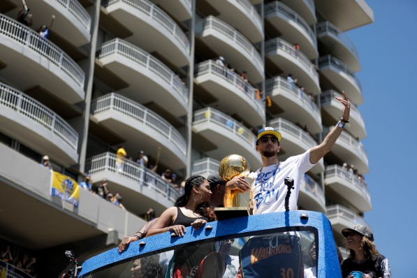Stephen Curry, right, tries to get the crowd going during the Golden State Warriors' championship parade in Oakland, Calif., on Tuesday, June 12, 2018. The Warriors recently swept the Cleveland Cavaliers in the NBA Finals to win their third championship in four years. (Randy Vazquez/ Bay Area News Group)
